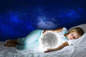 Girl lying in bed with moon in hands