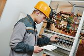 stock photo of fuse-box  - electrician builder engineer with blue print scheme project in front of fuse switch box - JPG