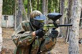 picture of paintball  - paintball sport player man in protective camouflage uniform and mask with marker gun outdoors - JPG