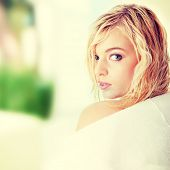 Young beautiful blond teen woman dressed in white bathrobe