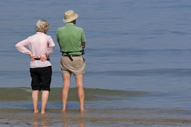 picture of retirement age  - Elderly man and woman standing together and paddling at the beach - JPG