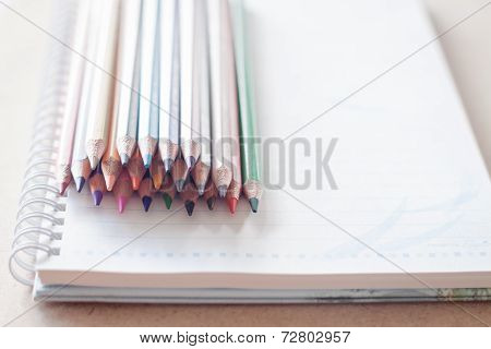 Cluster Of Colorful Pencil Crayons On Spiral Notebook
