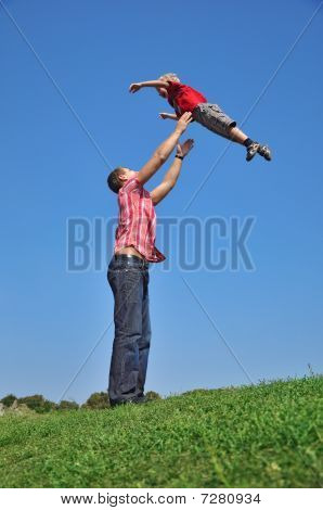 Father Throwing His Son In The Air And Catching Him