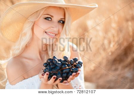Portrait of a beautiful young woman with a basket of grapes