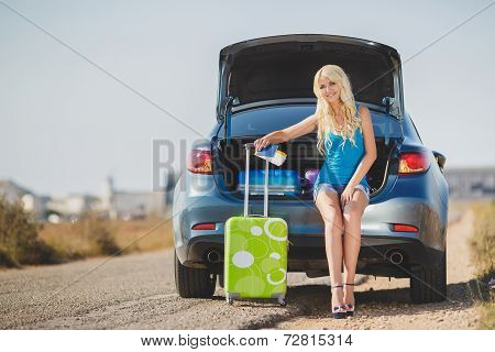 Young woman in anticipation of a trip outside his loaded cars