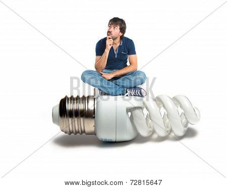 Man Thinking On Bulb Over White Background