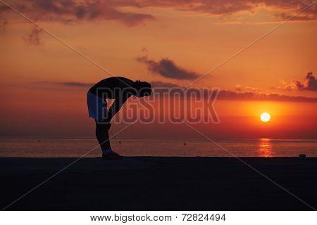 Tired after morning jogging athletic runner resting on the beach, male runner taking break