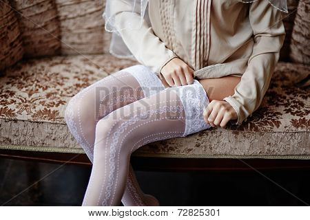 The girl puts on white stockings