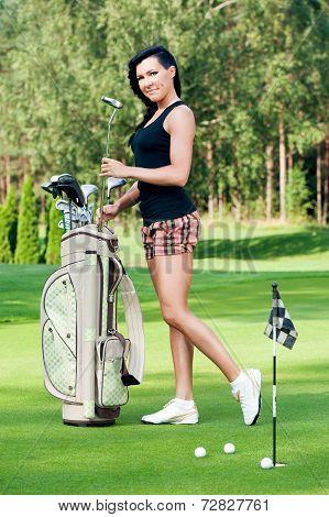 Sexy femail brunette golfer with golf equipment