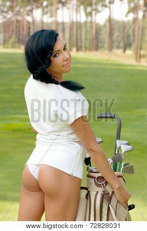 Attractive brunette golfer girl on golf course