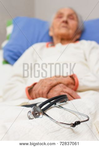 Elderly Woman Lying Ill In Her Bed With A Stehoscope