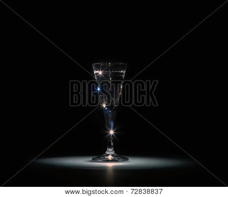 The glass of vodka stands in the dark on a light spot on a black background