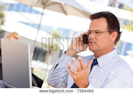 Businessman Talking On Cell Phone Using Laptop