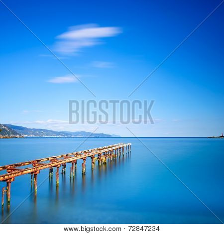 Wooden Pier Or Jetty Remains On A Blue Ocean Lake. Long Exposure.