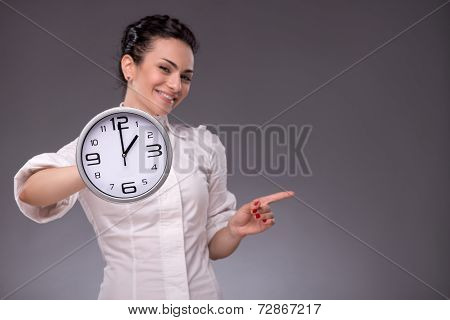 Portrait of nice girl holding big clock in her hands isolated on