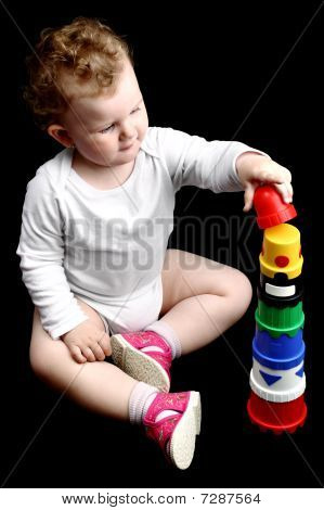Curly baby sitting on the floor building a tower with stacking nesting cups isolated on black