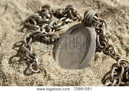 Rustic Pendant And Chain Buried In Sand