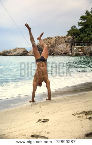Fit Muscular Man Doing A Handstand On The Beach