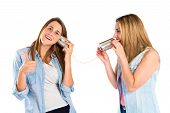 image of tin can phone  - Friends talking through a tin phone over white background - JPG
