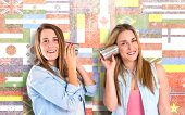 foto of toy phone  - Friends talking through a tin phone over flags background - JPG