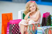 image of curio  - Little fashion girl with packages in a large shopping center - JPG