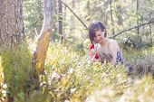 stock photo of breastfeeding  - youn mother breastfeeding her baby in the forest in springtime - JPG