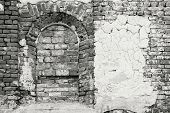 image of niche  - arch niche and the destroyed plaster on an old brick wall of the ancient building in monochrome tones - JPG