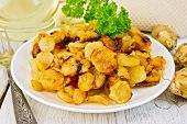 stock photo of jerusalem artichokes  - Jerusalem artichokes fried in a dish fresh tubers napkin parsley vegetable oil on a background of white wooden plank - JPG