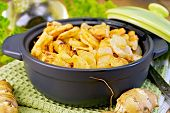 foto of jerusalem artichokes  - Jerusalem artichokes roasted in a roasting pan with a lid fresh tubers on a napkin parsley vegetable oil on a wooden boards background - JPG
