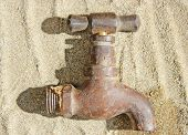 picture of scant  - An old brass water tap or faucet lying on sand.
