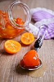 picture of kumquat  - Jam from the whole kumquats lies in the spoon against the background of the glass jar - JPG