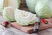 stock photo of cruciferous  - Cutted cabbage on cutting board with red chili peppers and knife on wooden background - JPG