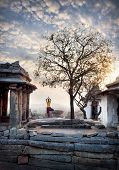 picture of karnataka  - Woman doing yoga near ancient ruins on Hemakuta hill in Hampi Karnataka India - JPG