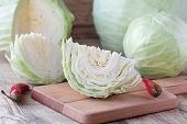 picture of cruciferous  - Cutted cabbage on cutting board with red chili peppers on wooden background - JPG