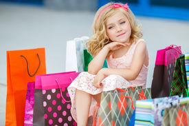 foto of curio  - Little fashion girl with packages in a large shopping center - JPG