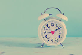 image of countdown  - Retro vintage style classic white alarm clock on vintage blue background for daylight saving or time concept - JPG