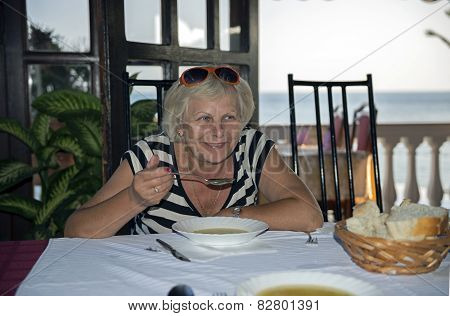 Woman Is Eating Soup At Resort Cafe.