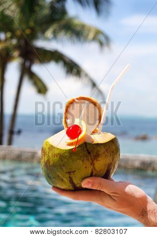 Man Holding Coconut Cocktail With Drinking Straw And Cocktail Cherry