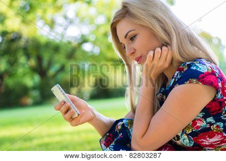 Woman in park online dating with smart phone