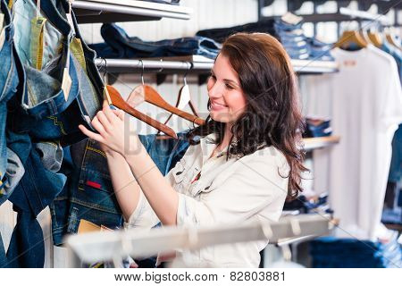 Woman buying blue jeans in shop