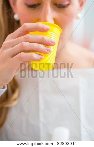 Patient rinse mouth with a cup of water at dentist