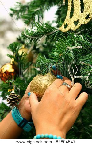 Hands Holding Of Various Decorations On The Christmas Tree.