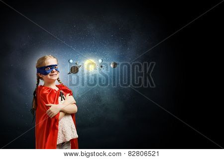 Cute girl in super hero costume exploring space system