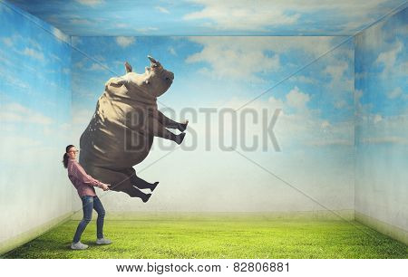 Funny young girl making effort to lift huge rhino