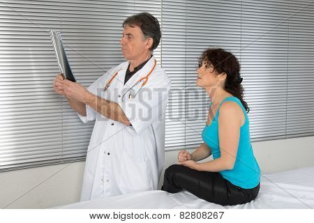 Male Doctors Pointing At His Patient X-ray Sheet In Clinic