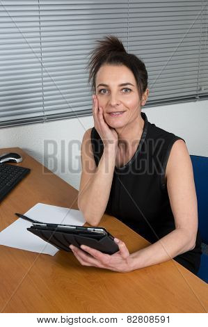 A Woman Sitting By Office Desk