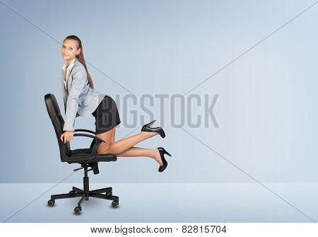 Businesswoman kneeling on office chair