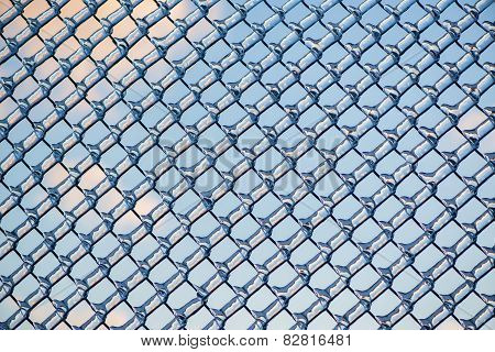 Refracted Clouds And Blue Sky Through Ice On Fence