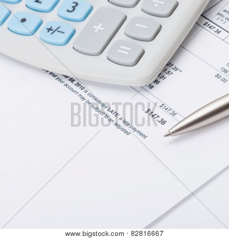 Studio Shot Of Calculator And Pen Over Some Receipt