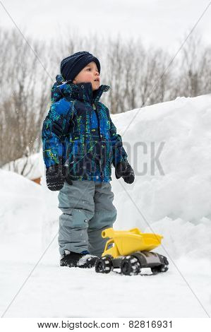 Boy With Toy Truck Beside Deep Snowbank